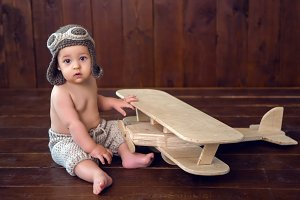 baby sits on the floor next to the wooden plane