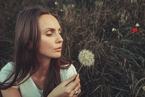 Beautiful Young Woman blowing on dandelion