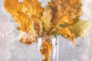 Yellow and orange autumn leaves in a glass on a wooden shelf.