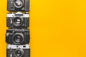 Vintage Film Cameras On Yellow Background Surface, Top View. Creativity Retro Technology Concept