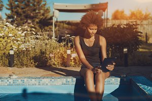 Girl with digital pad near pool