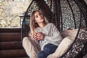 girl with a Cup of tea in a comfortable chair