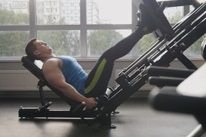 In the gym - muscular man exercising on leg press machine