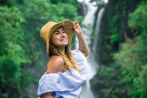 girl in hat looking at the waterfall
