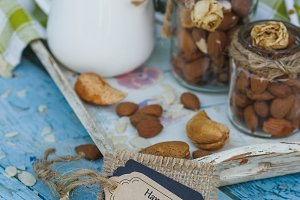 Almonds in the glass, jar with milk on the wooden tray, decorative tag