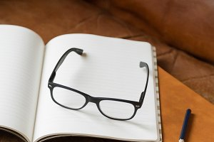 Glasses & Notebooks On Leather Couch