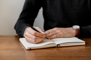 Man At Desk Writing In Notebook