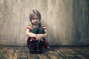 Sad little girl sitting on the floor