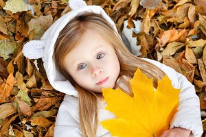 Little girl lying on fallen leaves