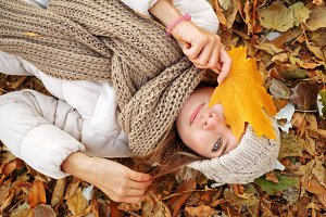Girl lying on fallen leaves