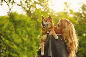 Girl and dog Shiba Inu embrace