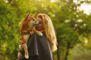 Girl and dog Shiba Inu hugging