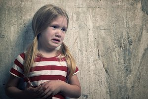 Little girl crying. Portrait of a child in tears. Background textured wall