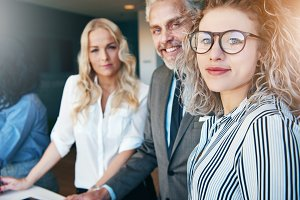 Smiling man and women looking at camera in office
