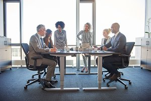 Diverse colleagues talking together in a boardroom in an office