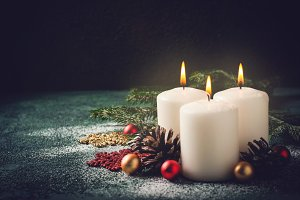 Three Christmas burning candles and decorations on dark  background