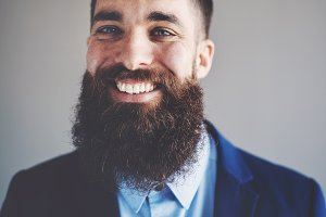 Smiling young entrepreneur with a long beard wearing a blazer