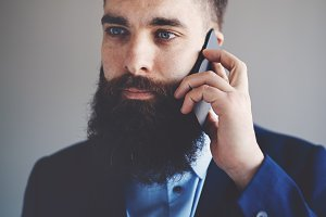 Young entrepreneur with a long beard talking on a cellphone