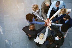 United businesspeople standing in a huddle with their hands together