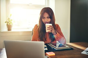 Focused young female entrepreneur drinking coffee while working at home