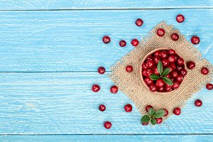 Cranberry with leaf in bowl on blue wooden background with copy space for your text. Top view