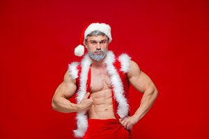 Christmas. Sport, activity. Sexy Santa Claus . Young muscular man wearing Santa Claus hat demonstrate his muscles. Isolated on red background