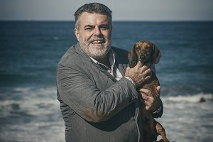bearded man on the coast With a dog