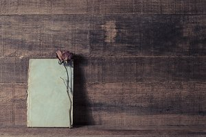 Old notebook and dry rose on wood