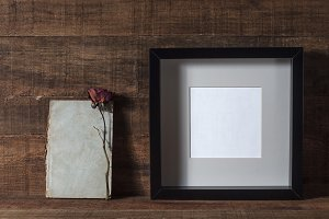 Blank photo frame and old notebook