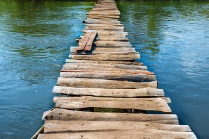 Old wooden bridge through river