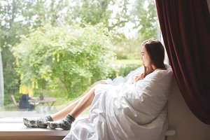 a woman sits on a windowsill