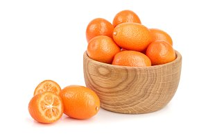 Cumquat or kumquat in wooden bowl isolated on white background close up