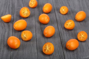 Cumquat or kumquat with half on bllack wooden background