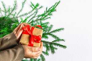 A gift in the hands of a girl against the background of fir branches. New Year Christmas.