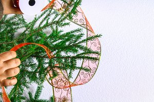 A girl is hanging a Christmas ribbon from the organza on a Christmas tree on a white background.