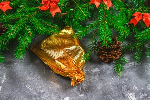 Fir branches with cones and red bows on top of a gray concrete background. New Year Christmas. Gold bag with gifts.