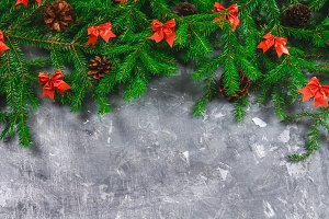 Fir branches with cones and red bows on top of a gray concrete background. New Year Christmas. Free space for text.