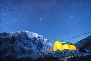 Yellow glowing tent against high rocks with snowy peak and sky w