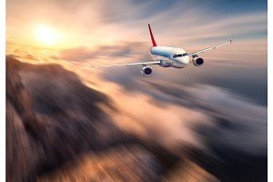 Amazing airplane mith motion blur effect is flying over low clouds