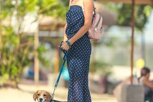 Young woman with her lovely beagle dog in the park of Bali island, Indonesia.