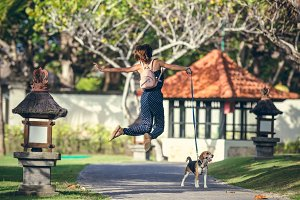 Young woman jumping with her lovely beagle dog in the park of Bali island, Indonesia.