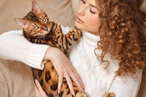 Girl hugging Bengal cat.
