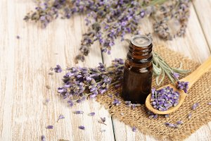 Herbal oil and lavender flowers on wooden background