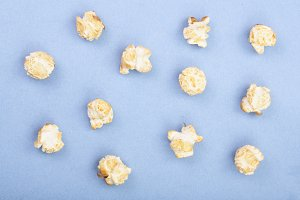 Popcorn on blue background. Top view. Flat lay pattern