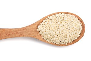 Sesame seeds in a wooden spoon isolated on white background top view