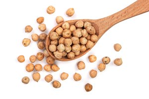 Dry raw organic chickpeas in a wooden spoon isolated on white background. Top view