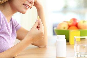 Girl hand taking vitamin pill