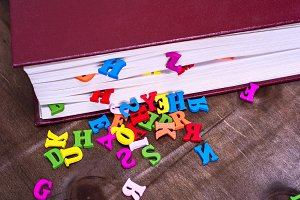 multicolored letters and book