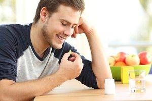 Happy man taking omega 3 pill