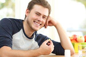 Happy man holding omega 3 pill